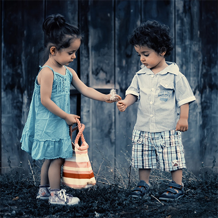 Photo of two children sharing flowers